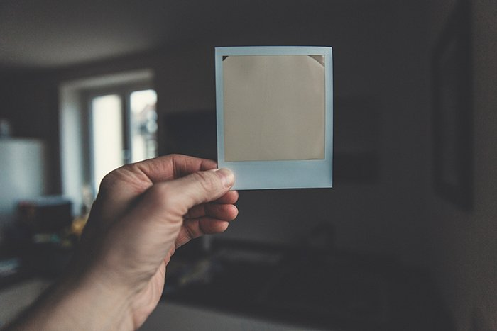 A persons hand holding a polaroid - instant photography