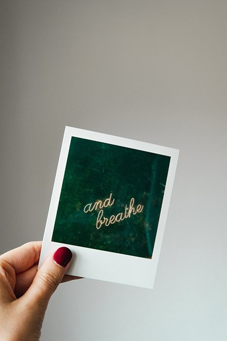 A hand holding a polaroid photo of the words 'don't breathe' on dark green background