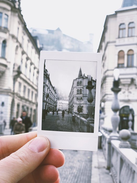 A person holding an instant photo of a cityscape within an actual cityscape