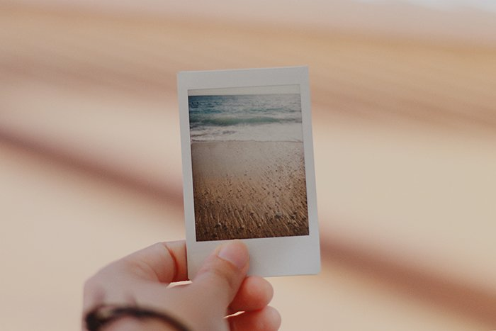 A persons hand holding an instant photo of a beach