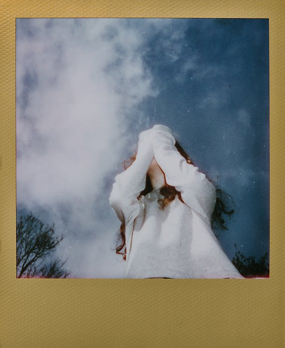 Dreamy instant photography portrait of a female model outdoors