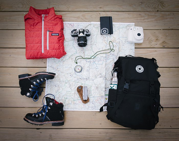A flat lay of an instant camera, instant photography gear and accessories laid out on a map