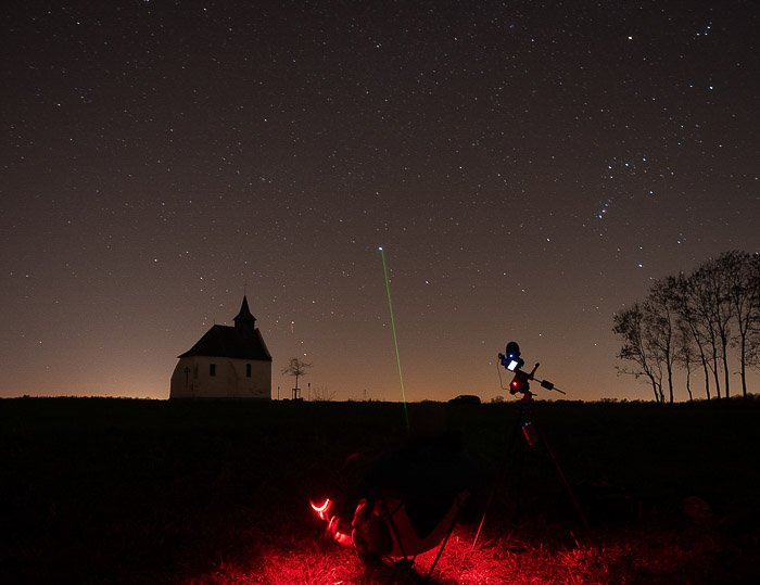 A classic starry landscape. The moderate light pollution is visible as orange glow at the horizon.