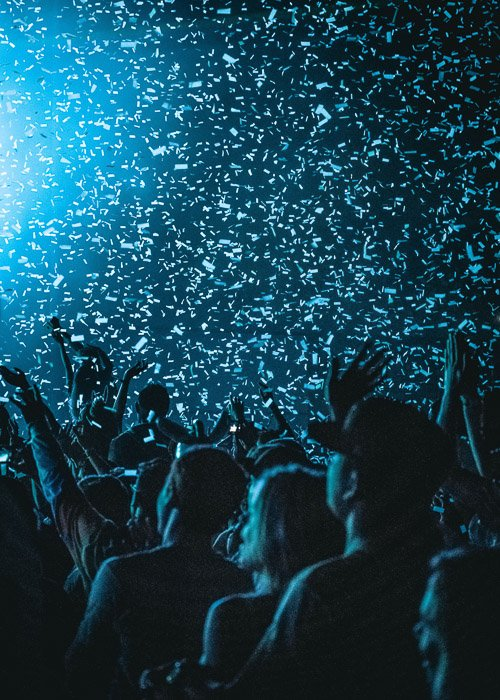 low light shot of confetti falling on the crowd at a fashion show