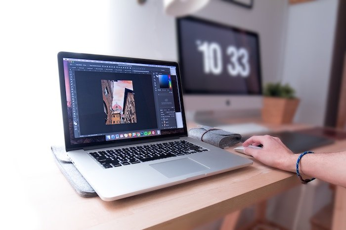 A person using Lightroom on a laptop in a home office