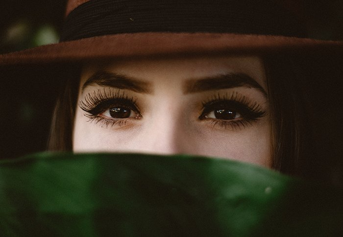 Striking portrait of a female model with fake eyelashes posing for a makeup photography shoot