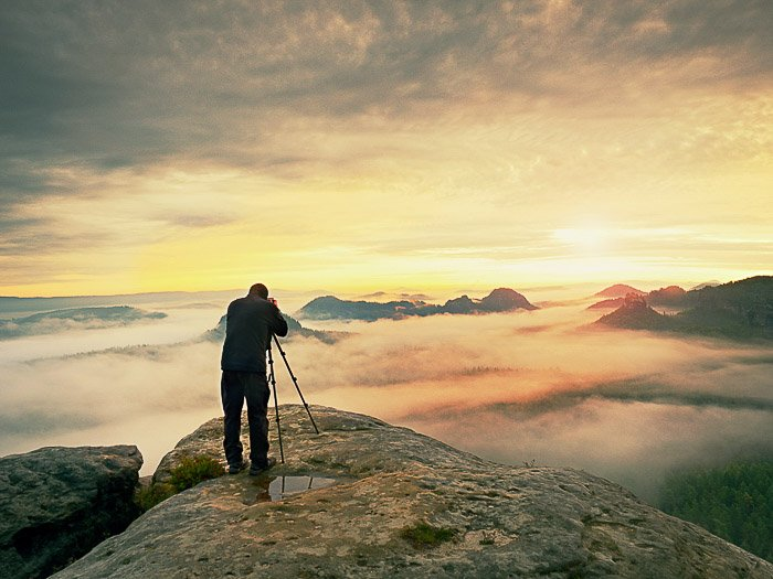 A man shooting images of fog in a landscape