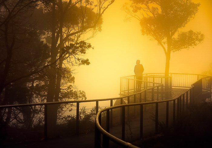 A person on a bridge in a foggy landscape at sunset