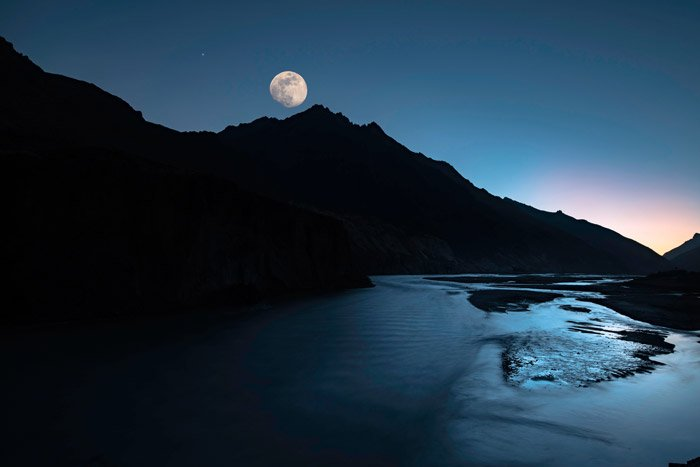 the moon above a beautiful mountainous landscape by a lake - stunning landscape photos