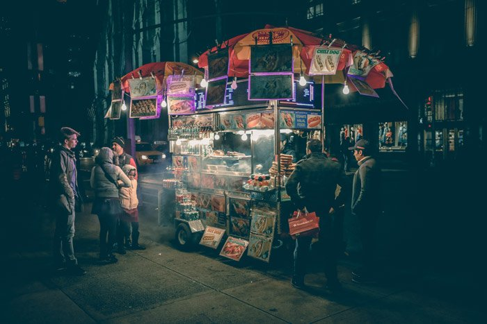 Street portrait of people at an outdoor food stall at night - photography themes