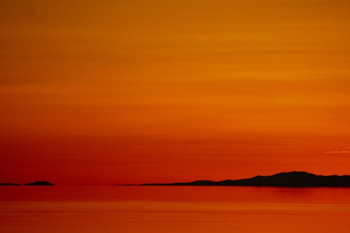 a beautiful orange and red colored coastal scene at sunset- stunning landscape photos