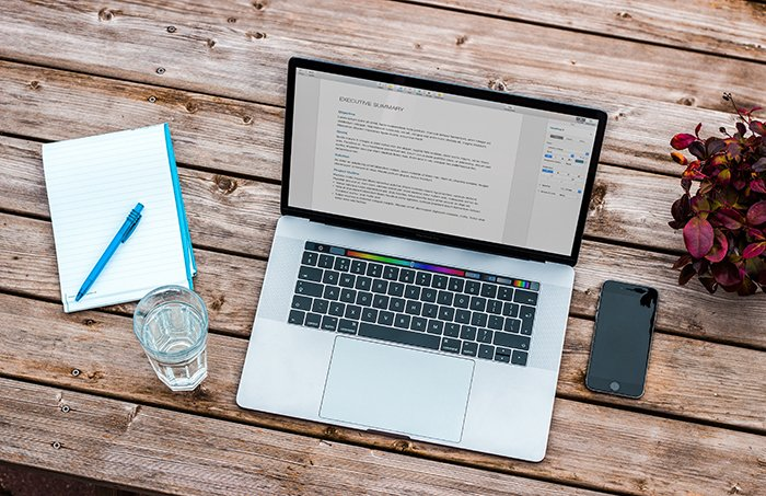 A laptop, phone and notebook on a wooden table
