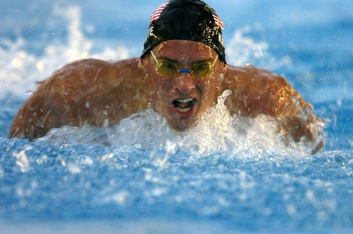 a face on view of a male swimmer in action