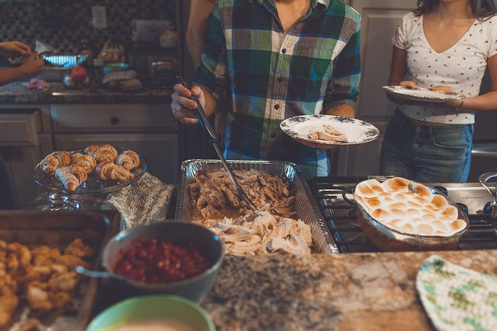 Candid thanksgiving picture of people serving themselves food