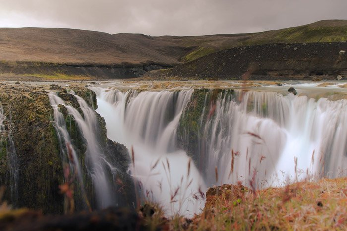 a dreamy mountainous landscape over a waterfall - stunning landscape photos