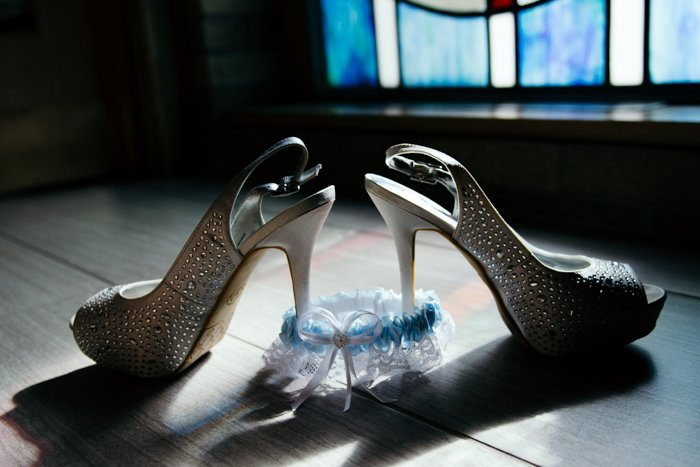 atmospheric still life of wedding shoes and garter on the floor - wedding photography business tips