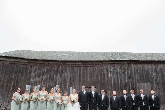 a wedding portrait of the wedding party posing in front of a rustic wooden building - wedding photography business tips