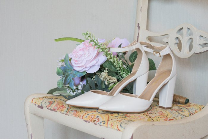 atmospheric still life of wedding shoes and flowers on a chair - wedding photography business tips