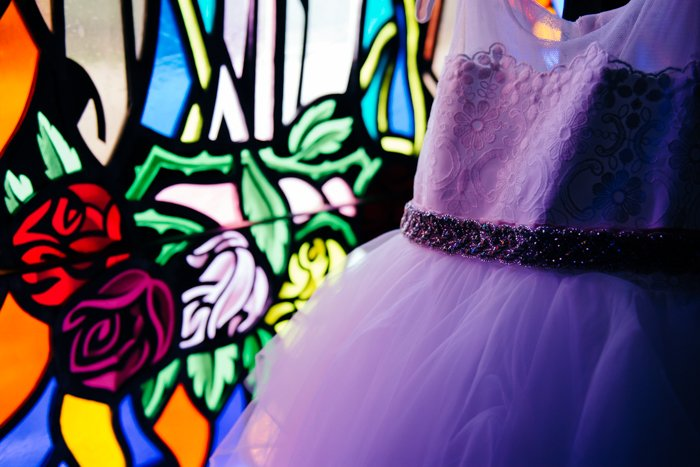 Wedding portrait of a purple bridesmaids dress in front of stained glass - wedding photography business tips