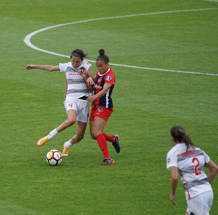 A soccer photography shot of female players mid-match