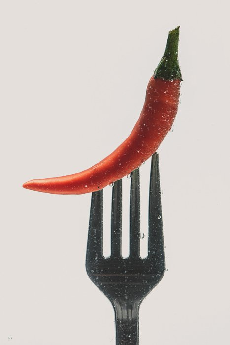 a chilli pepper on a fork - setup to shoot colorful paint in water photography