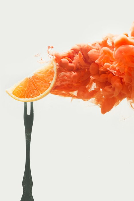 an orange slice on a fork - setup to shoot colorful paint in water photography