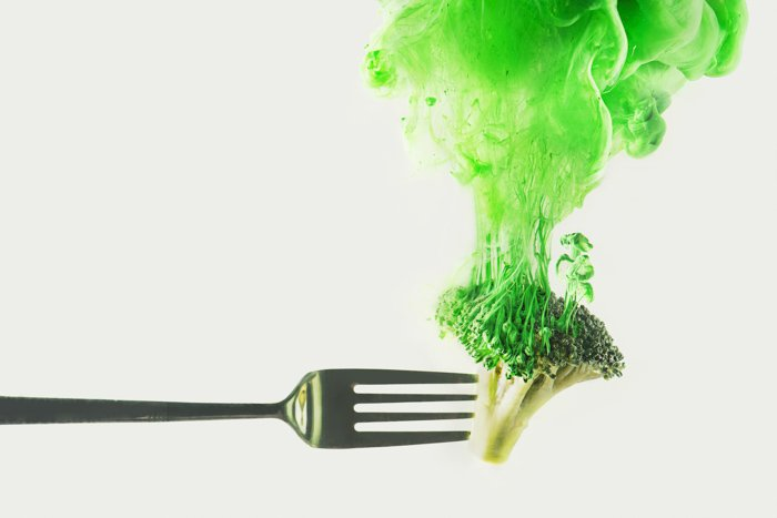 A fork of broccoli with green cloud shot using colorful paint in water technique