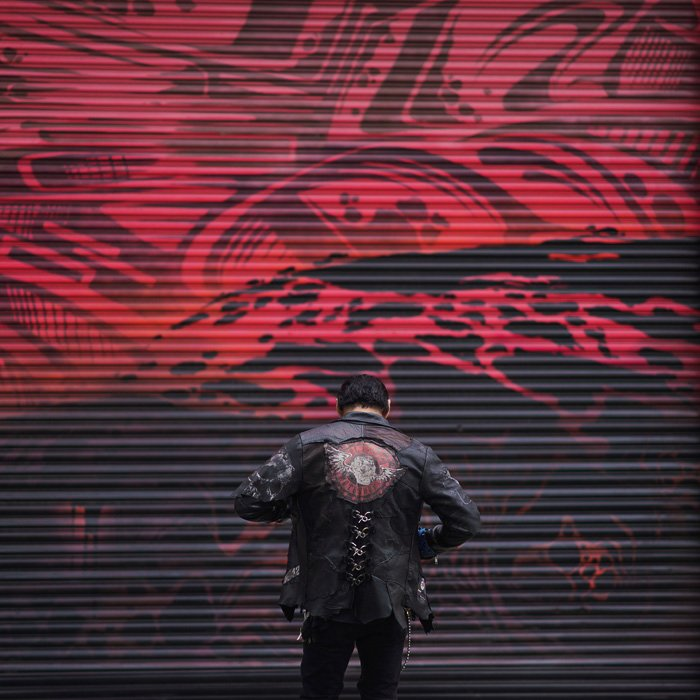 Atmospheric portrait of a male model posing moodily by a graffiti painted wall