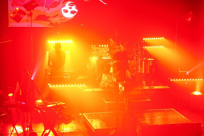 Atmospheric concert photo of a stage lighted with electric red and yellow light