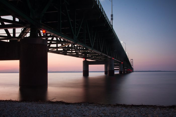 a dramatic photo of a bridge over a river at sunset, utilizing dynamic range in photography