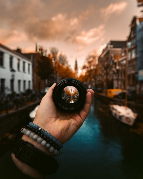 Creative photo of a person holding a camera lens in front of the camera at Groenburgwal, Amsterdam