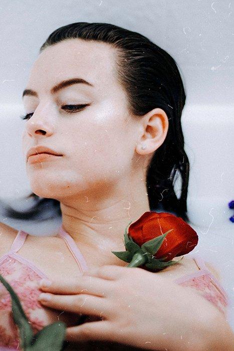 sensual milk bath portrait of a female model using boudoir photography props