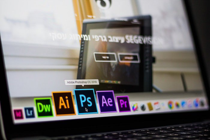 a close up of a person choosing the photoshop icon on a laptop to edit ecommerce photography