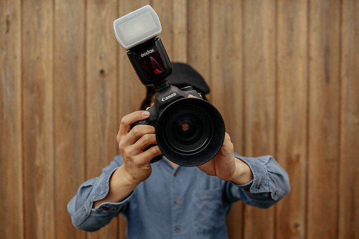 A photographer holding a dslr camera with a flash diffuser attached