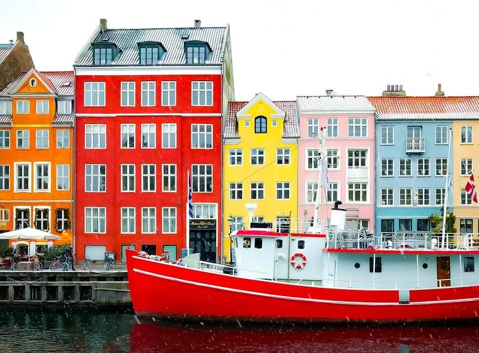 Photo of a ship with colorful houses in the background