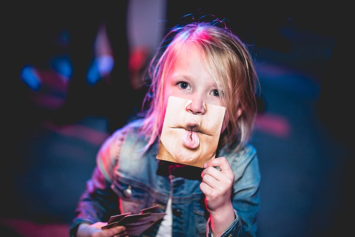 A funny photography portrait of a child holding a photo of a funny mouth to their own