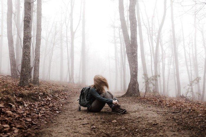 坐在森林里的一个女孩的大气画象编辑了使用lightroom脱落特征