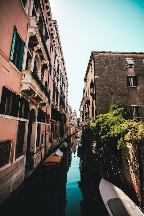 boats in canals running through narrow streets, utilizing the teal and orange color scheme