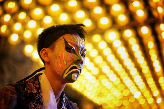 A man dressed up for carnival with distinctive bokeh background created using a wide aperture