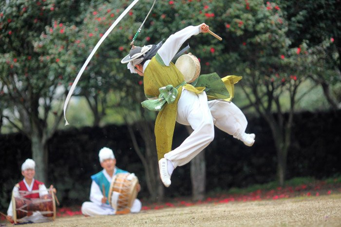A traditional dancer in mid air - wide vs narrow aperture