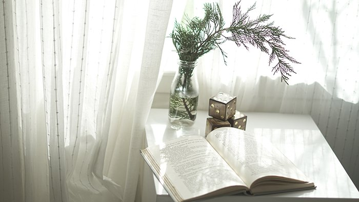 Dreamy still life of a book and bouquet of flowers on a white table