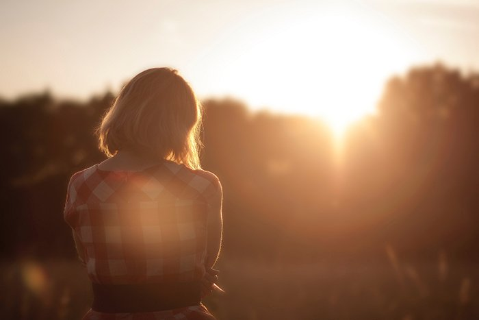 dreamy shot of a person standing in a field at sunset