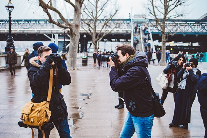 a group of people shooting aesthetic street photography images outdoors