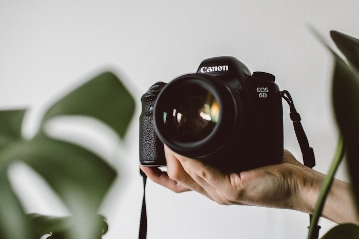 a hand holding a canon DSLR camera - photography business tools
