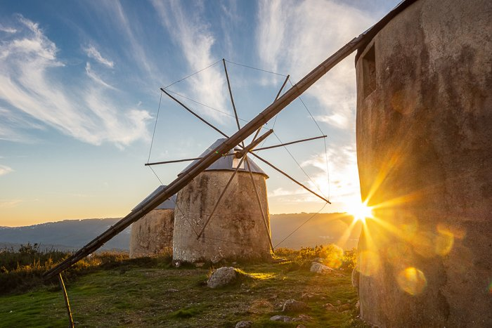 A stone windmill in a green landscape with a starburst effect