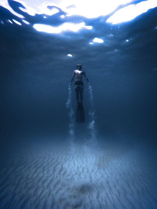 an underwater portrait of a diver with subtle vignette on the image