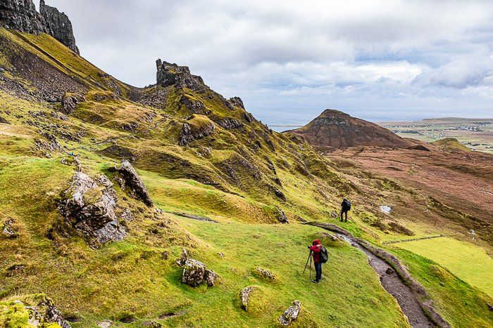 hikers walking through a mountainous landscape - adventure photography skills