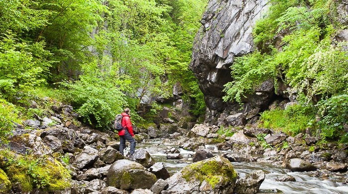 a hiker admiring a waterfall - adventure photography skills