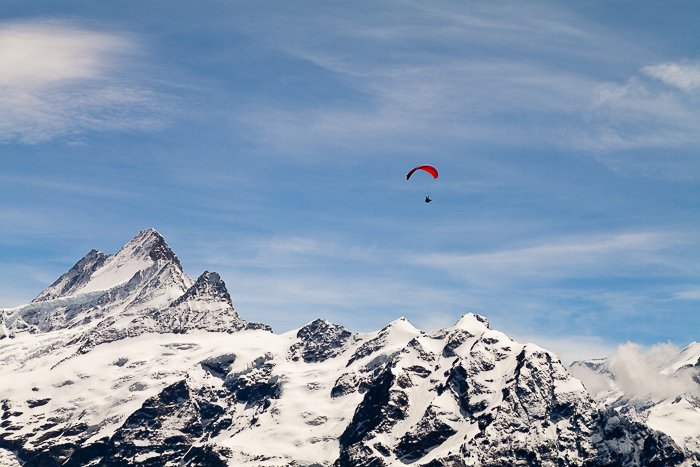 a paraglider sailing over snow covered mountains - adventure photography skills