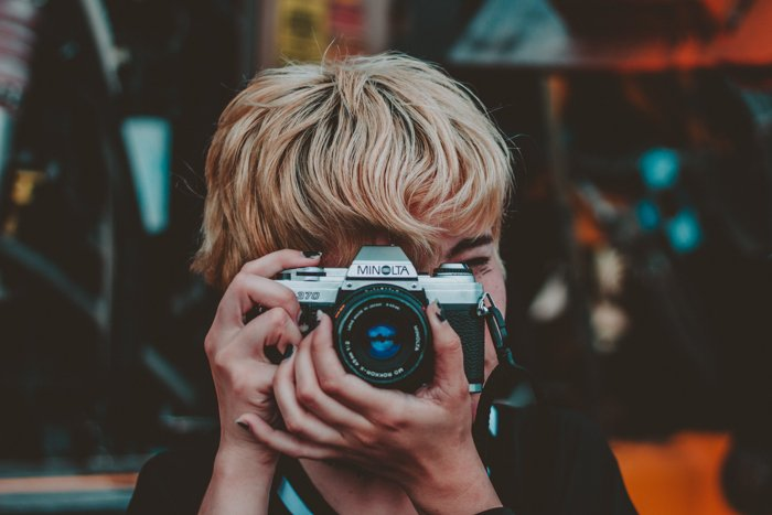 a female photographer shooting with a minolta camera - find camera manuals online